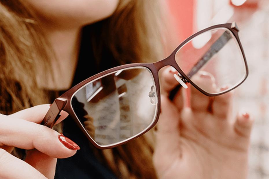 A imagem mostra uma mulher segurando um óculos de armação quadrada e marrom